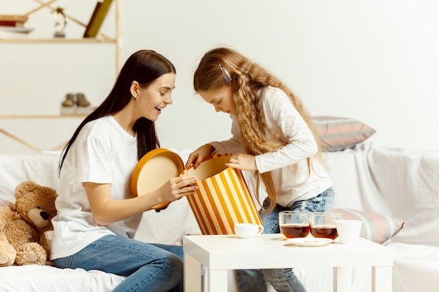Little girl and her attractive young mother sitting on sofa with gift and spending time together at home. generation of women. international women's day. happy mother's day.