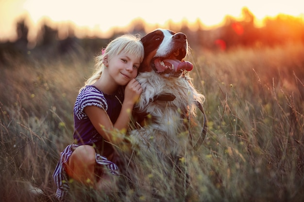 Little girl and her dog are walking in the meadow in the tall grass at sunset.