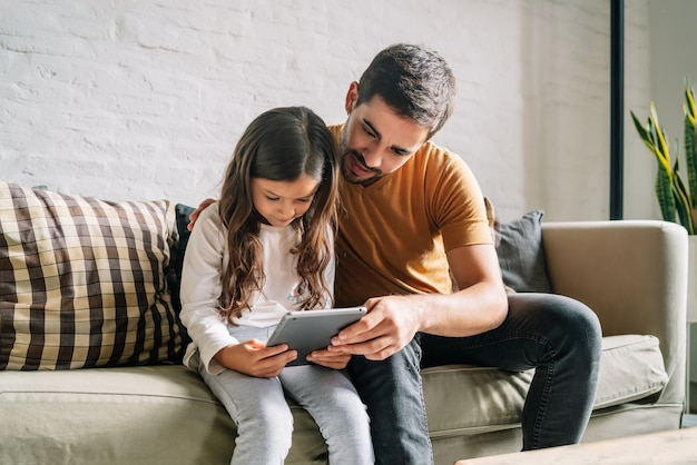 Little girl and her father having fun together while playing with a digital tablet at home. monoparental family concept.
