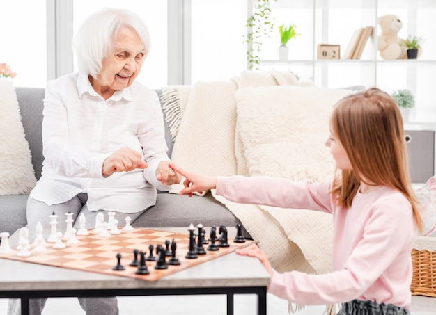 Little girl and her grandmother making decision who go first in chess game