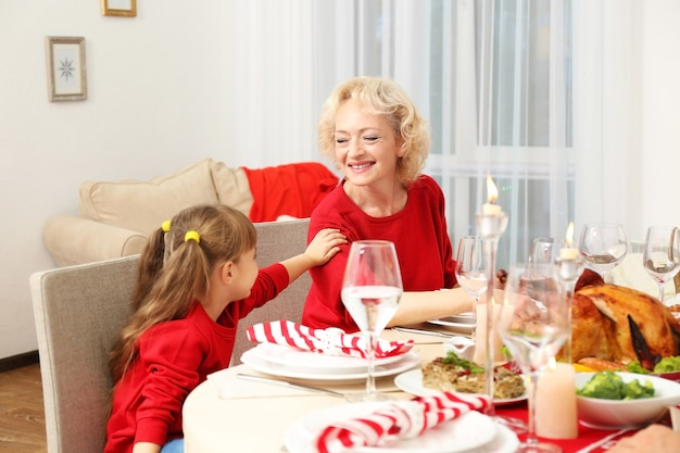 Little girl and her grandmother sitting at table during thanksgiving dinner