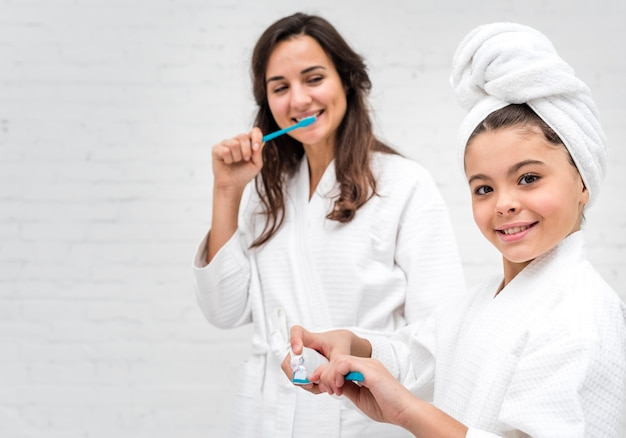Little girl and her mom brushing their teeth