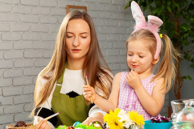 Little girl and her mother coloring eggs for easter together