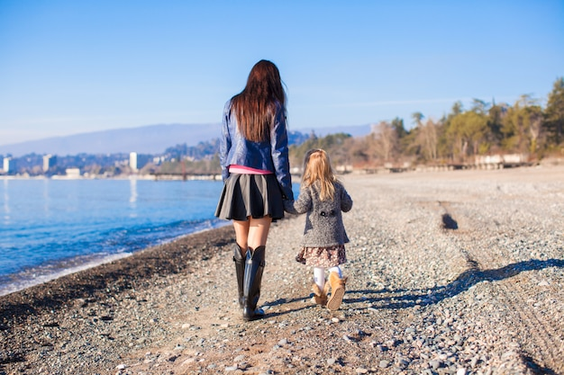 Little girl and her mother walking on the beach in winter sunny day