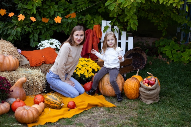 Little girl and her mother with pumpkins