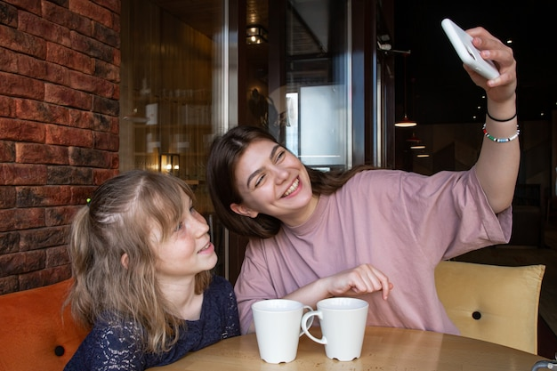A little girl and her older sister are taking a selfie in a cafe