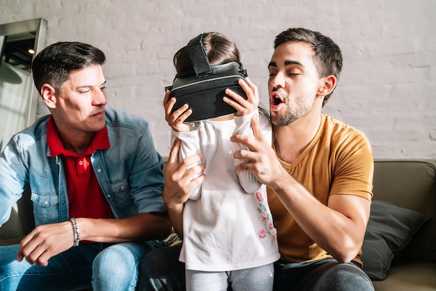 Little girl and her parents playing video games with vr glasses at home. family concept.
