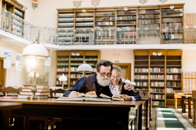 A little girl and her senior bearded grandfather are reading books, sitting at the table with many books and vintage desk lamp in old ancient library