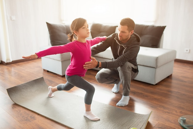 Little girl and her young father are doing lunge forward workout at home.