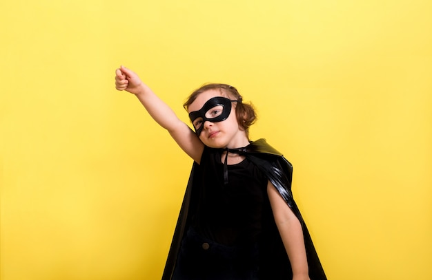 Little girl hero in a mask and cape on a yellow wall