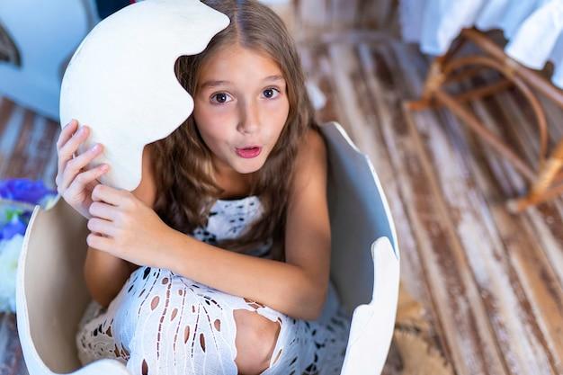 小さな女の子が巨大なおもちゃの卵から殻に隠れました