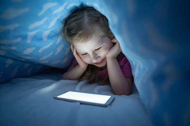 Little girl hides under blanket with smartphone at night when everyone asleep.