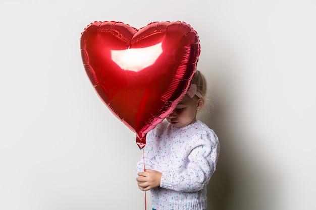 밝은 배경에 심장 공기 풍선 뒤에 숨어있는 어린 소녀. 발렌타인 데이, 생일에 대한 개념입니다. 배너.
