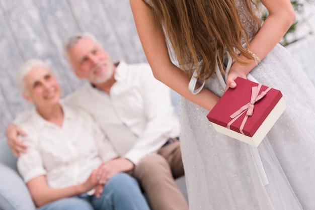 Маленькая девочка прячет подарок за спиной перед бабушкой и дедушкой, сидя на диване