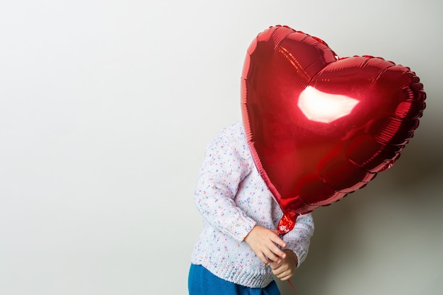 Little girl hiding behind a heart air balloon on a light background. concept for valentine's day, birthday. banner.