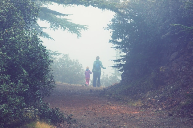 Маленькая девочка, путешествующая пешком по тропе в лесу.
