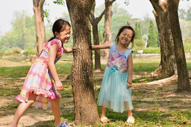 Little girl and his sister play in summer park