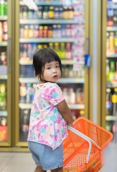 小さな女の子がバスケットを持って買い物にミニマートで歩く