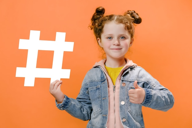 Little girl hold white hashtag icon and with her thumb up isolated on orange background