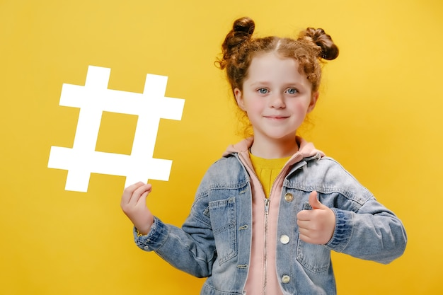 Little girl hold white hashtag icon and with her thumb up isolated on yellow background