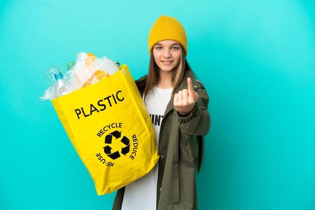 ペットボトルでいっぱいのバッグを持って、次のジェスチャーをしている孤立した青い背景の上にリサイクルする少女