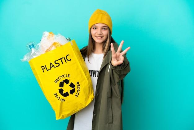 幸せな孤立した青い背景の上にリサイクルするためにペットボトルでいっぱいのバッグを持って、指で3を数える少女