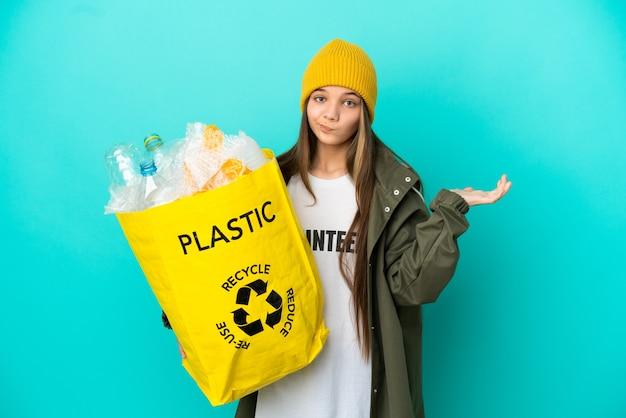 手を上げている間疑問を持っている孤立した青い背景の上にリサイクルするためにペットボトルでいっぱいのバッグを持っている少女