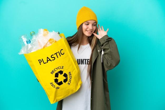 Маленькая девочка держит мешок, полный пластиковых бутылок для переработки на изолированном синем фоне, слушая что-то, положив руку на ухо