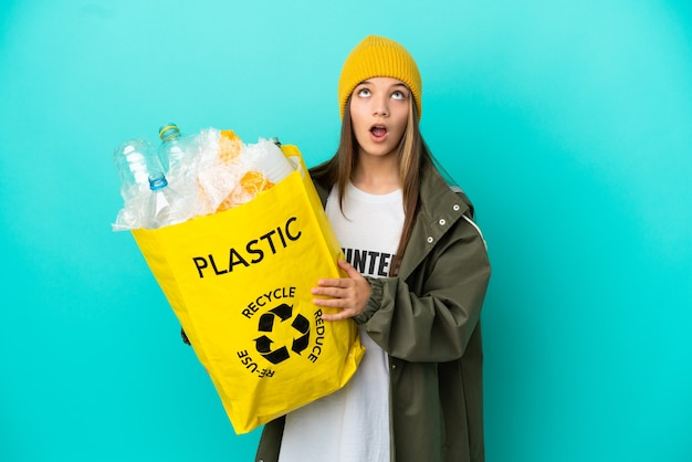 ペットボトルでいっぱいのバッグを持って、孤立した青い背景を見上げて驚いた表情でリサイクルする少女