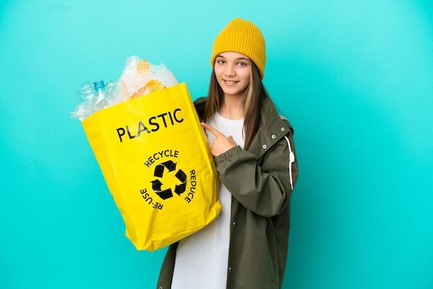 제품을 제시하기 위해 측면을 가리키는 고립된 파란색 배경 위에 재활용하기 위해 플라스틱 병으로 가득 찬 가방을 들고 있는 어린 소녀