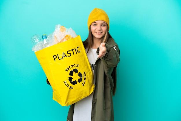 격리된 파란색 배경 위에 재활용하기 위해 플라스틱 병으로 가득 찬 가방을 들고 있는 어린 소녀가 좋은 거래를 성사시키기 위해 악수를 하고 있습니다