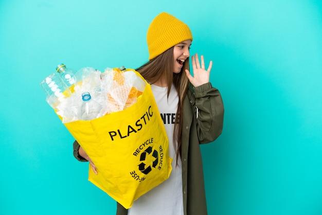 Маленькая девочка держит мешок, полный пластиковых бутылок для переработки на изолированном синем фоне, кричит с широко открытым ртом