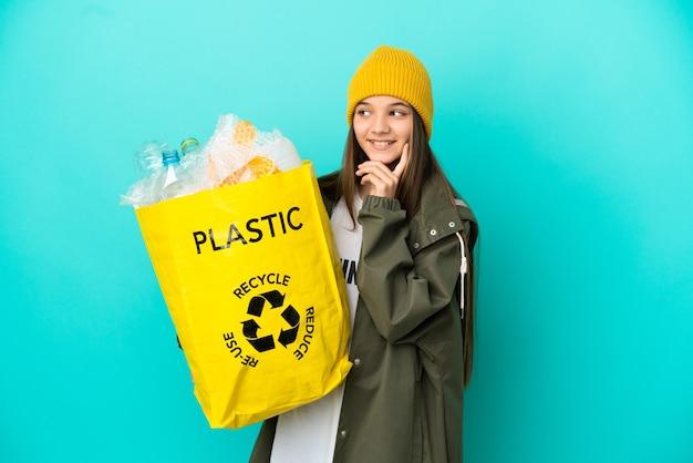 ペットボトルでいっぱいのバッグを持って、見上げながらアイデアを考えて孤立した青い背景の上にリサイクルする少女