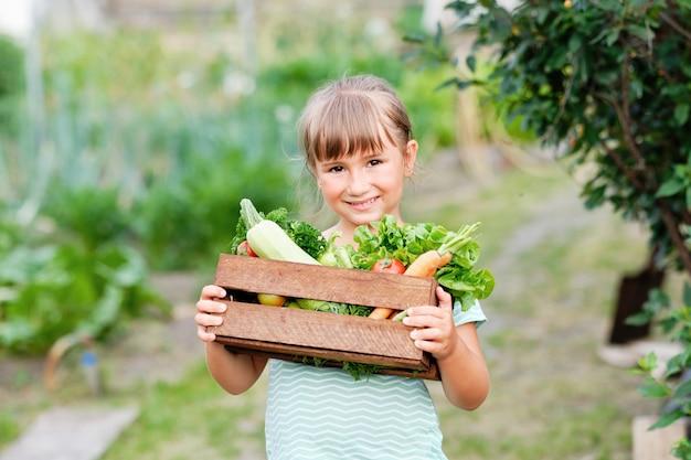 有機バイオファームで収穫有機野菜と根でいっぱいのバスケットを持っている少女。秋の野菜の収穫。