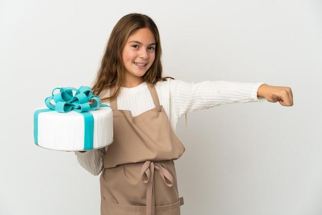 孤立した白い背景の上に大きなケーキを持った少女が親指を立てるジェスチャーを与える