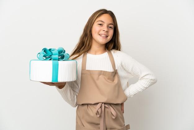 腰に腕と笑顔でポーズをとって孤立した白い背景の上に大きなケーキを保持している少女