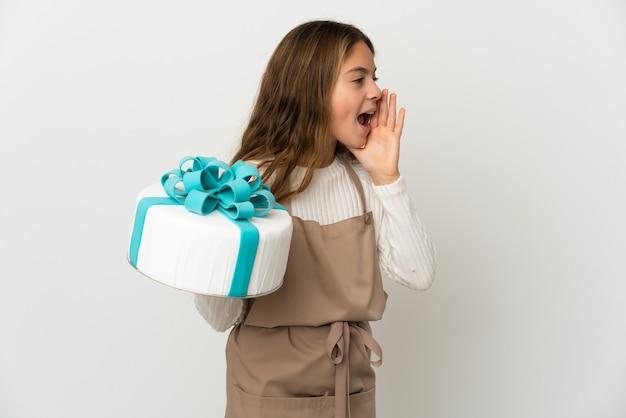 Маленькая девочка держит большой торт на изолированном белом фоне, кричит с широко открытым ртом в сторону