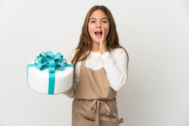 Маленькая девочка держит большой торт на изолированном белом фоне и кричит с широко открытым ртом