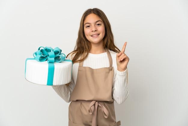 孤立した白い背景の上に大きなケーキを持って、最高の兆候を示して指を持ち上げる少女