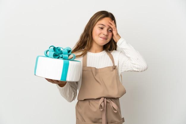 Маленькая девочка держит большой торт на изолированном белом фоне, много улыбаясь