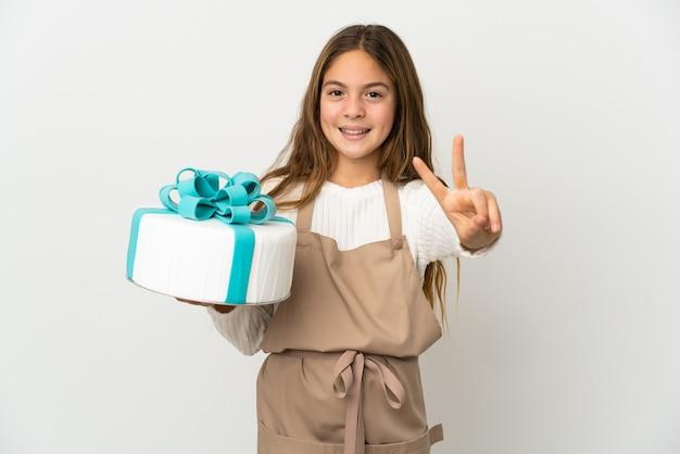 웃 고 승리 기호를 보여주는 격리 된 흰색 배경 위에 큰 케이크를 들고 어린 소녀
