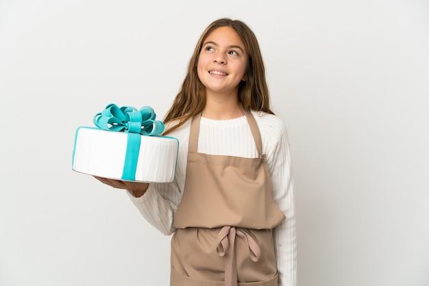 Маленькая девочка держит большой торт на изолированном белом фоне, думая об идее, глядя вверх
