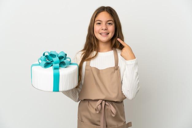 親指を立てるジェスチャーを与える孤立した白い壁の上に大きなケーキを保持している少女