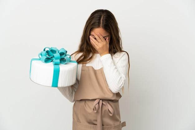 疲れて病気の表情で孤立した白の上に大きなケーキを保持している少女