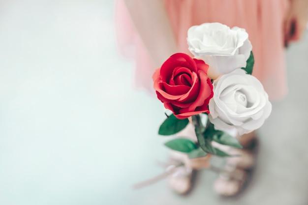 美しいバラの花束を保持している小さな女の子