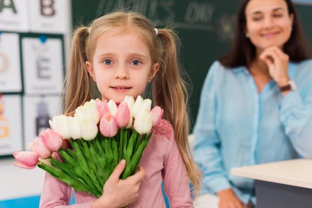 彼女の先生のための花の花束を保持している小さな女の子