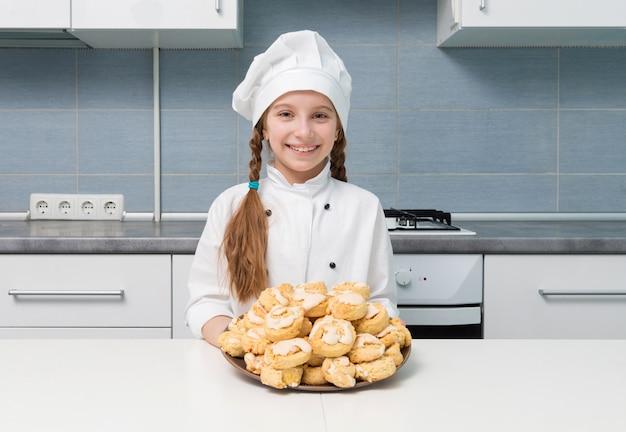 自家製クッキーのボウルを保持している小さな女の子