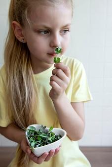 Маленькая девочка держит в руках миску с микрозеленью. концепция здорового питания