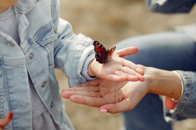 Маленькая девочка держит бабочку