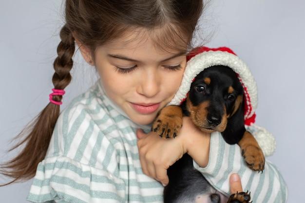 彼女のサンタ帽子ペットの新年の贈り物にダックスフントの子犬を保持している少女